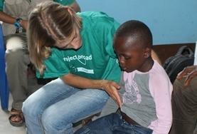 Behutsam korrigiert unsere Physiotherapie - Praktikantin die Sitzhaltung ihrer kleinen Patientin in Togo.
