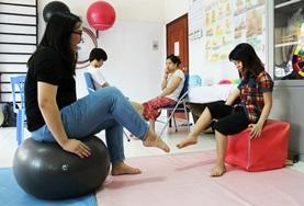 Im Therapieraum in einer physiotherapeutischen Praxis in Hanoi macht unsere Praktikantin eine Fußübung vor.