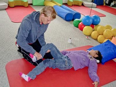 Eine Freiwillige und ein junger Patient im Physiotherapie – Praktikum in Bolivien