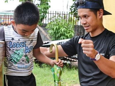 Ein junger Patient auf den Philippinen bekommt eine Physiotherapie - Sitzung von einem Freiwilligen
