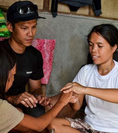 Ein Freiwilliger zeigt der Mutter einer jungen Patienten auf den Philippinen Physiotherapie - Übungen für zu Hause