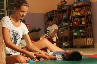 Eine Freiwillige behandelt ein Kleinkind in Kambodscha