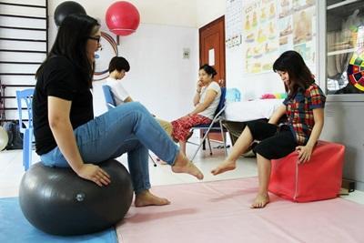 Praktikantin macht Übungen mit einem Kind in einer physiotherapeutischen Einrichtung in Vietnam