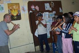 Eine Gruppe von Schüler/innen präsentiert ein Musikstück während eines Projekttages, das sie zusammen mit unseren Freiwilligen im Musik - Pädagogik - Projekt eingeübt haben.