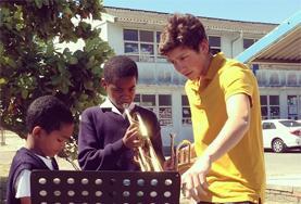 Ein Freiwilliger gibt eine Unterrichtsstunde in Südafrika im Musik - Projekt in Kapstadt.