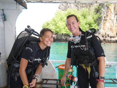 Zwei Freiwillige bereiten sich mit Tauchausrüstung auf einem Boot auf den Tauchgang vor