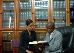 Eine Freiwillige lässt sich im Jura - Praktikum in Ghana vom Staatsanwalt ihrer Praktikumskanzlei in Details der Gesetzestexte einführen.