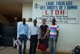 Freiwillige und Mitarbeiter/innen vor einer unserer Partnerorganisationen im Togo, der Vereinigung für Menschenrechte Togos.