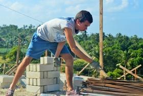 Ein Freiwilliger im Schulferien - Special Hausbau auf den Philippinen packt beim Aufbau eines Dachfirstes mit an.