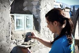 Eine Freiwillige verputzt ein neu gesetztes Fenster im Hausbau - Projekt für Schüler/innen im wunderschönen Kapstadt in Südafrika.