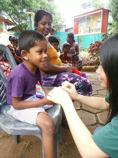 Schulferien - Volontärin behandelt einen Jungen im Medizin - Projekt in Sri Lanka