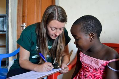 Schülerin untersucht eine junge Patientin im Schulferien-Special in Arusha