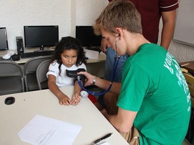 Ein Freiwilliger von Projects Abroad im Public Health Projekt misst den Blutdruck eines kleinen Mädchens