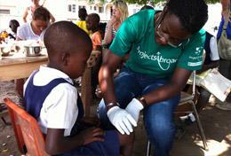 Während unserer Gesundheitskampagne auf dem Land in Ghana verarztet eine Schülerin im Schulferien - Special Medizin die Schürfwunde eines Schulkindes.