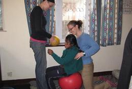 Eine Freiwillige unterstützt eine Therapiesitzung im Behandlungszentrum einer Reha-Klinik in Nepal, in der Schüler/innen in ihren Schulferien in die Welt der Physiotherapie hineinschnuppern können.