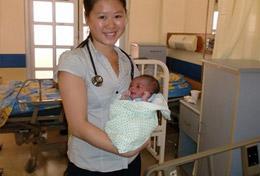 Ein Neugeborenes auf dem Arm unserer Schulferien - Special Freiwilligen, die in Jamaika erste medizinische Erfahrungen sammelt.