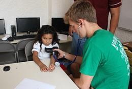 Ein Schüler lernt im Schulferien - Special Public Health in Mexiko, wie man richtig den Blutdruck eines Patienten misst.