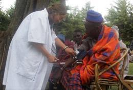 Eine Freiwillige im Schulferien - Special in Tansania misst den Blutdruck eines Massai beim Medical Outreach auf dem Land.