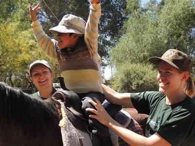 Ein Junge aus Bolivien nimmt an einer Pferdetherapie-Stunde mit Freiwilligen in Cochabamba teil.