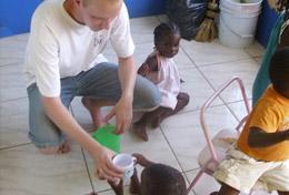 Ein Freiwilliger gibt einem kleinen Kind etwas zu Trinken im während seines Freiwilligendienstes in seinen Schulferien auf Jamaika.
