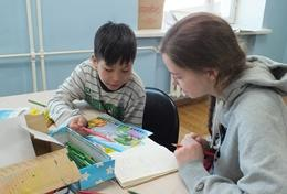 Eine Freiwillige hilft einem mongolischen Schüler mit den Hausaufgaben im Schulferien - Special Soziale Arbeit in der Mongolei.