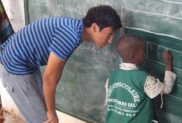 Schreibübungen in der Vorschule: im Senegal übt ein Schüler zusammen mit einem Freiwilligen das Schreiben verschiedener Buchstaben.