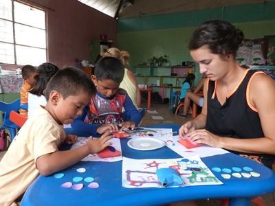 Zwei Kinder in Ecuador basteln mit einer Frewilligen zusammen