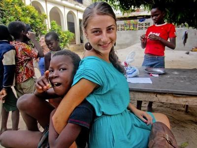 Eine Freiwillige umarmt ein Kind in Togo