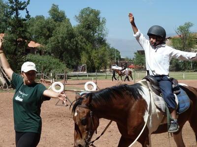 Ein Kind übt mit einer Freiwilligen das Gleichgewicht auf einem Pferd