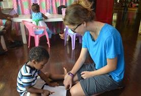 Eine Freiwillige beschäftigt ein Kind in der Kindertagesstätte in Montego Bay spielerisch.
