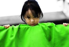 Ein kleines Mädchen in der Kindertagesstätte in Cebu lugt für unsere Freiwillige im Sozialarbeits - Projekt in die Kamera.