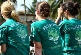 Freiwillige in Togo sitzen während eines Medical Outreaches für ihre Pause auf einer Bank und tauschen sich über ihre Erfahrungen mit den Patient/innen aus.