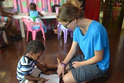 Freiwillige hilft einem kleinen Jungen beim Schreiben auf Jamaika