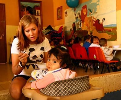 Eine Freiwillige füttert ein Kind in Mexiko