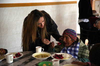 Eine Freiwillige hilft einer alten Dame beim Mittagessen im Seniorenheim in Cusco