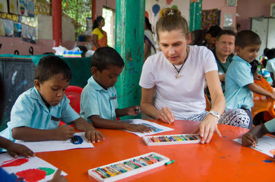 Eine Freiwillige hilft den Kids mit Wachsmalstiften ein Bild zu malen