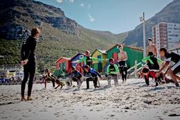 Freiwillige im Surf - Projekt bei Aufwärmübungen mit den Surfschüler/innen am Strand von Muizenberg.