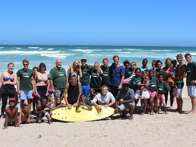 Freiwillige und Surfschüler des Sport-Projekts am Strand in Muizenberg, Südafrika.