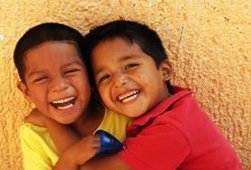 Zwei Schüler einer Grundschule lachen in San Pedro für eine Freiwillige in die Kamera.