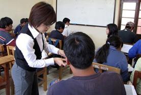 Eine Freiwillige im Klassenzimmer mit Schüler/innen, denen sie im Fach Englisch Nachhilfe gibt.