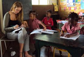 In einer Grundschule korrigiert unsere Freiwillige die Hausaufgaben ihrer Englisch - Klasse.