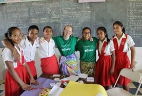Zwei Freiwillige aus Europa und Asien leisten einen Freiwilligendienst im Unterrichts - Projekt in Samoa und posieren hier mit ihrer Klasse für ein Foto.