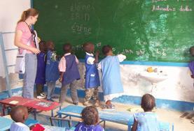 Eine Freiwillige wird im Unterrichts - Projekt im Senegal als Lehrerassistentin tätig und beaufsichtigt Schreibübungen ihrer Schüler/innen an der Tafel.