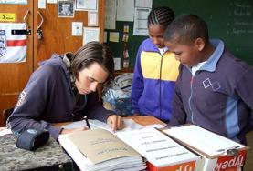 Ein Freiwilliger korrigiert während seines Freiwilligendienstes in Südafrika die Hausaufgaben seiner Schulklasse.