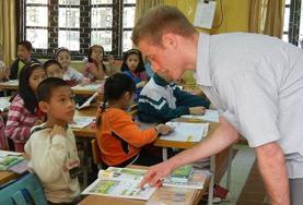 Ein Freiwilliger geht im Unterrichts - Projekt in Vietnam verschiedene Vokabeln mit einem Schüler durch.