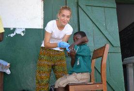 Eine Freiwillige versorgt die Schürfwunde eines Jungen während ihrer Freiwilligenarbeit über Weihnachten und Neujahr in Ghana.
