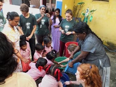 Freiwillige von Projects Abroad im Winter – Special helfen Kindern beim Händewaschen in Sri Lanka