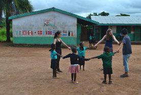 In unserer sozialen Partnereinrichtung in Ghana singen zwei Freiwillige zusammen mit den Kindern im Schulhof ein Lied.