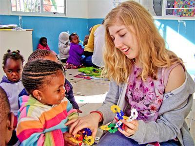 Eine Freiwillige mit Kind im Winter-Special Sozialarbeit und Community Work in Südafrika
