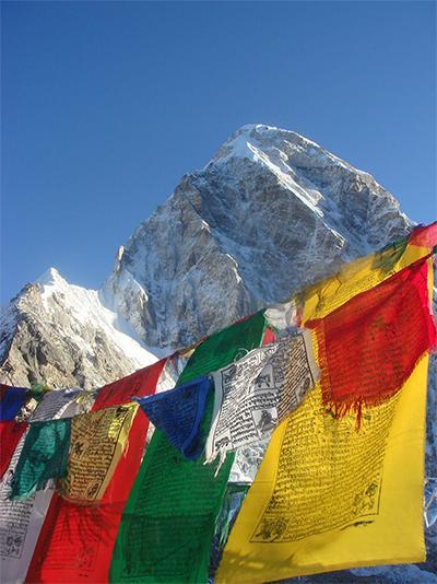 Bunte Gebetsfahnen wehen vor schneebedecktem Gipfel in Nepal